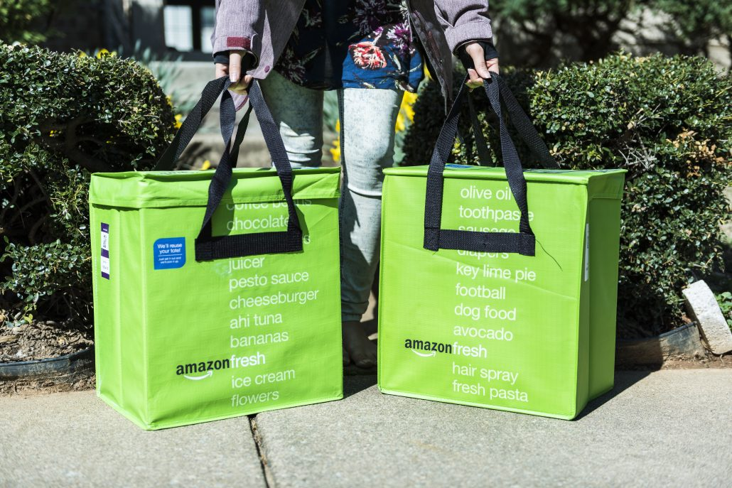 Amazon Fresh insulated grocery delivery bags on front porch closeup with woman picking them up.